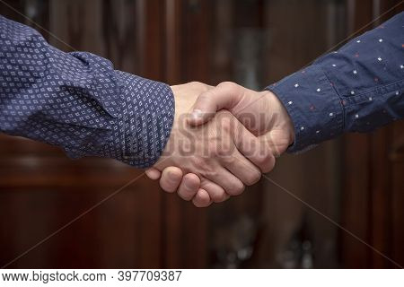 An Elderly Man Shakes Hands With A Young Business Partner. Concept: Conclusion Of A Transaction Or C