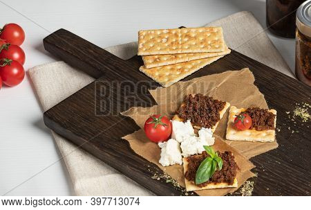 Crackers With Tomato Pate And Feta Cheese On Dark Wooden Cutting Board, Quick And Healthy Snacks Con