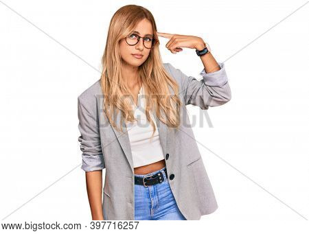 Beautiful blonde young woman wearing business clothes pointing unhappy to pimple on forehead, ugly infection of blackhead. acne and skin problem
