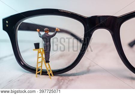 Optician Eyeglasses Being Cleaned By Tiny Figurine Symbolizing Clear Vision