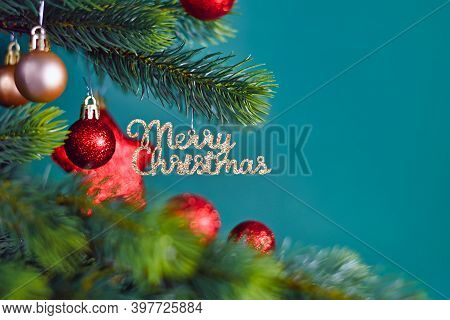 Golden Christmas Tree Ornament With Text 'merry Christmas' Hanging From Fir Tree Branch With Red Rou