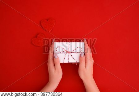Females Hands Holding White Gift Box With Hearts Decoration On Red Background. Christmas, New Year,