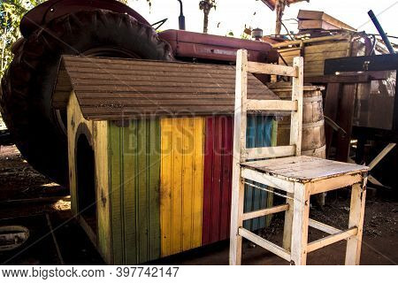 Abandoned Pile Of Paraphernalia (chairs, Tractor, Vibrant Colored Dog House And More) At A Shed