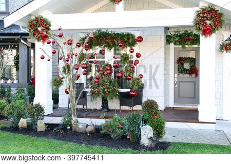Contemporary Christmas decorations on the front porch of a Canadian home. New house with festive red bauble ornaments and greens for the holidays.