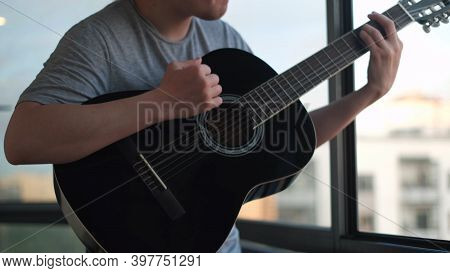 Close Up Of Lonely Man Playing Guitar Against An Opened Window. Concept. Young Musician Playing Chor