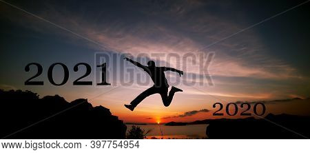 New Year 2021 Concept Of Silhouette Travel Man Jumping On The Cliff In Sunrise Or Sunset Time To 202
