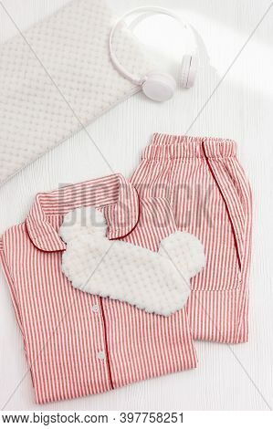 Comfort Pink Pajama, Headphones, Cushion, Fluffy Sleeping Eye Mask On White Wooden Background. Acces
