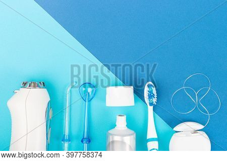 Toothpaste, Toothbrush And Dental Irrigator On Blue Background, Copy Space.