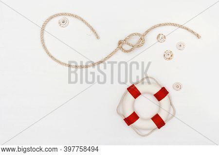Flat Lay Of Rope With Sea Knot And Life Preserver. Copy Space.