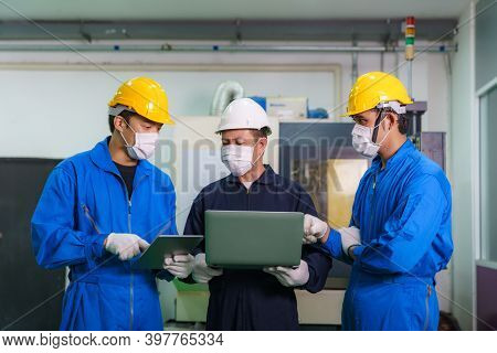 Asian Industrial Engineers And Worker In Hard Hats Discuss Product Line In Laptop And Make Showing G