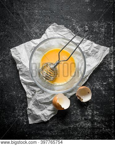 Beaten Egg In A Bowl With A Whisk On Paper. On Dark Rustic Background
