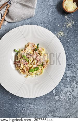 Pasta Carbonara with Bacon and Microgreens. Garnished with Parmesan Cheese