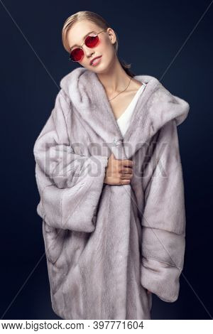 Fur coat fashion. Fashionable young woman model posing in an expensive blue mink fur coat on a dark blue background.