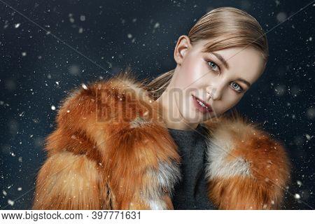 Portrait of a happy cute girl in a fox fur coat on a dark blue background with snow. Winter fur coat fashion.