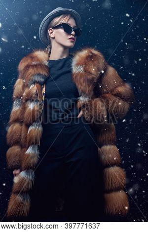 Fashion model posing in a luxurious fox fur coat on a dark blue background with snow. Winter fur coat fashion.