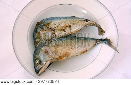 Two Fried Mackerel In The White Dish. A Migratory Surface-dwelling Predatory Fish, Commercially Impo