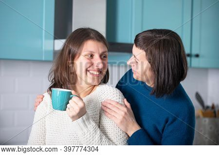 LGBT lesbian happy couple having morning coffee together in the kichen. LGBT lesbian couple together indoors concept.