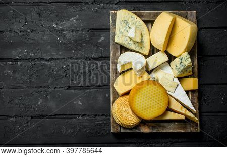 Assortment Of Different Types Of Cheese In A Wooden Box. On Black Rustic Background.