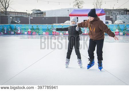 On A Frosty Winter Day, Brother And Sister Go Ice Skating On The Ice Rink. They Are Holding Hands. B