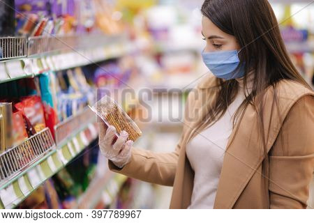 Horizontal Shot Of Woman In Protective Mask And Gloves Reading Label With Price At Goods While Stand