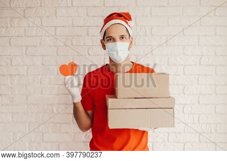 Happy Delivery Guy In Medical Face Mask, Protective Gloves Hold Cardboard Packages, Heart Sign In Ha