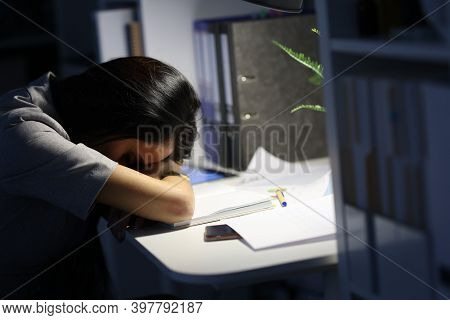 Woman Putting Her Head On Documents At Table In Office. Workload Of Employees Concept