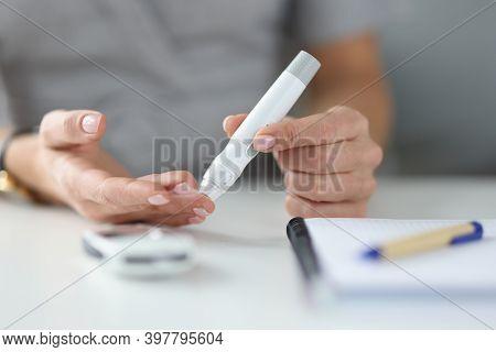 Woman Holding Lancet Near Her Finger To Measure Blood Glucose Closeup. Diabetes Mellitus Treatment C