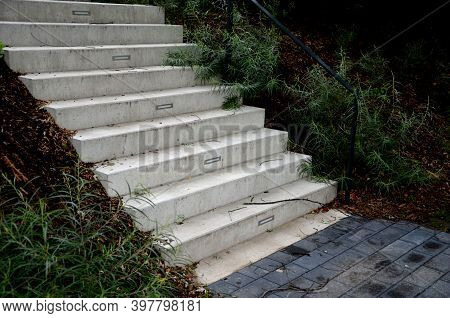 Bright Monolithic Concrete Park Staircase With Stair Lighting With Metal Railing Black Interlocking