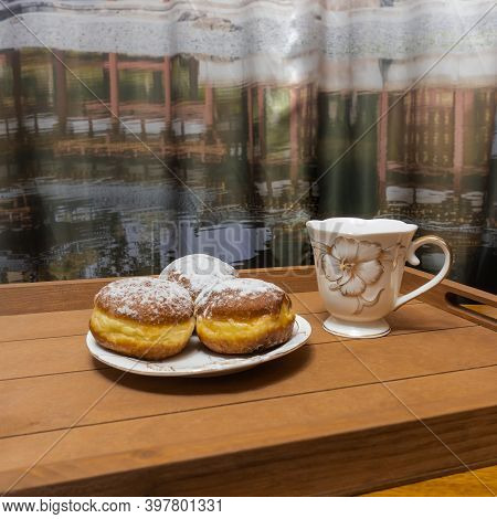 On A Brown Wooden Tray Are White Crockery With Golden Floral Designs. On The Saucer Are Three Donuts