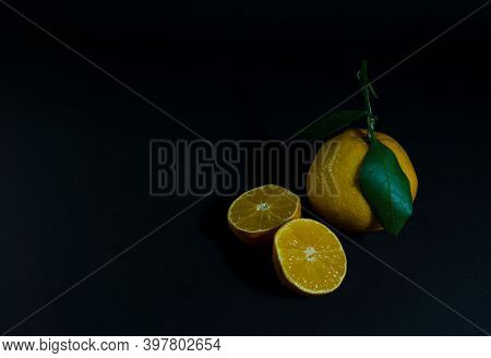 Tangerine Cut With A Green Leaf On A Black Background