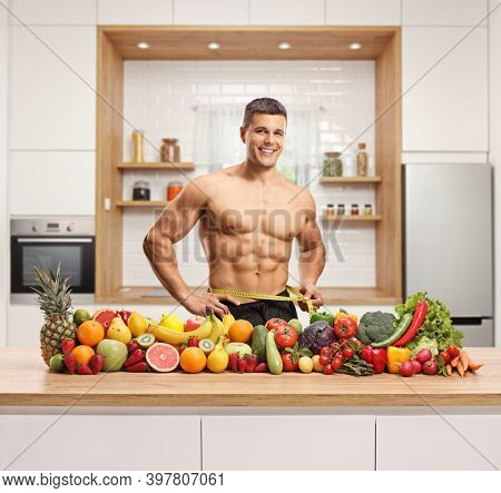 Man measuring his waist and posing with a pile of healthy fruits and vegetables on a counter in a modern kitchen