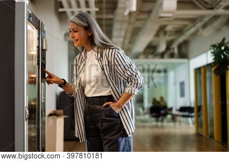 Happy white-haired mature woman using vending machine and smiling indoors