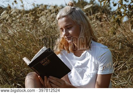 Christian Teenage Girl Reading The Bible In The Field. Faith, Spirituality And Religion Concept. Pea