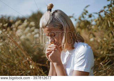 A Teenage Girl Closed Her Eyes While Praying In A Field. Hands Folded In Prayer Faith, Spirituality