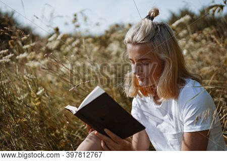 Teenage Girl Reading The Book In The Field. The Girl Sitting On A Grass, Reading A Book. Rest And Re