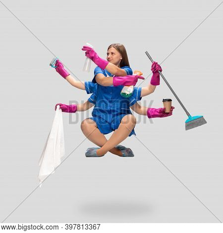 Multitask. Female Housemaid In Blue Uniform And Pink Gloves Like Shiva Isolated On Gray Background.
