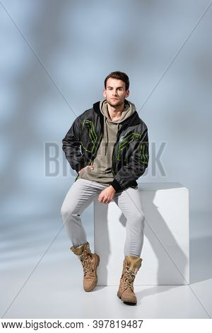 Trendy Man In Hoodie And Parka Posing While Sitting On White Cube On Grey