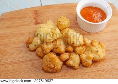 Florets Of Battered Cauliflower Served With A Spicy Tomato Dipping Sauce