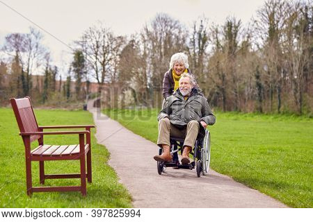 Senior Woman Pushing Senior Man In Wheelchair Outdoors In Fall Or Winter Park