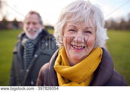 Portrait Of Loving Senior Couple Enjoying Autumn Or Winter Walk Through Park Together