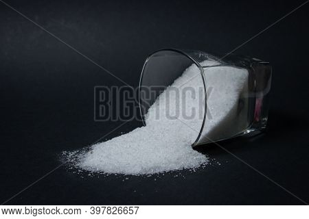 Salt On A Black Background. The Salt Poured Out Of The Glass. Excessive Salt Intake. Coarse Salt