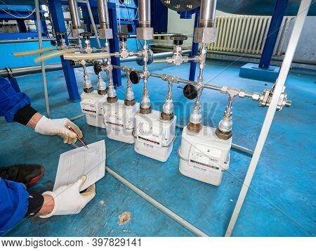 Worker Checks Methane Gas Consumption On Gas Flow Meters. Industrial Gas Meter And Consumption Meter