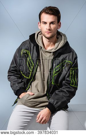 Man In Hoodie And Parka Posing While Sitting On White Cube Isolated On Grey