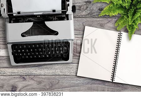 Blogging Or Writing Concept, Directly Above View Of Old Typewriter And Blank Open Note Pad On Wooden
