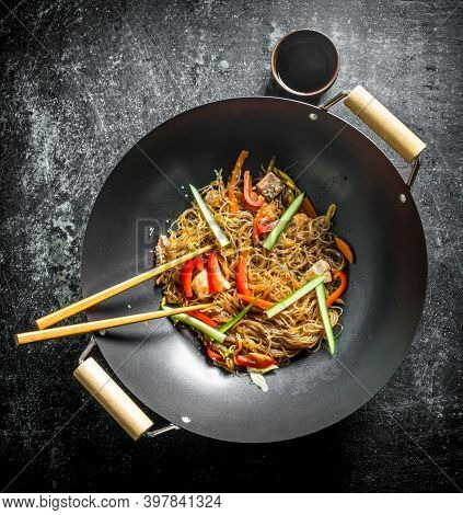 Chinese Wok. Asian Cellophane Noodles With Vegetables And Chicken In A Frying Pan Wok. On Dark Rusti