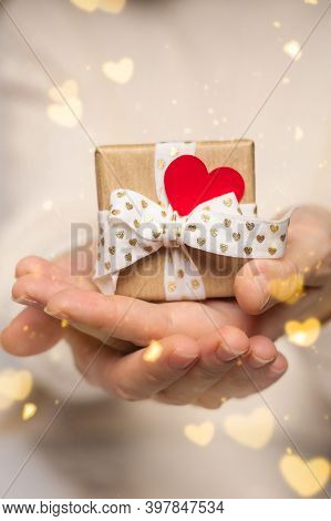 Beauty Woman Hands Holding Gift Box With Red Heart On Pink Glow Bokeh Background, Close-up. Pastel C