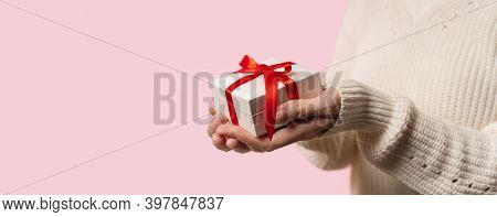Beauty Woman Hands Holding Gift Box With Red Bow On Pink Background, Close-up. Pastel Colors, Copy S