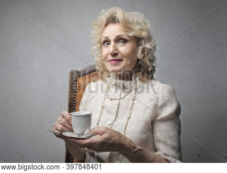 portrait of an elderly lady while drinking a cup of coffee