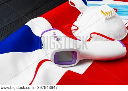 Medical Face Mask And Contactless Thermometer On British Flag