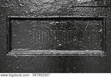 Part Of An Old Glossy Black Painted Door With An Element In The Form Of A Rectangular Frame For The